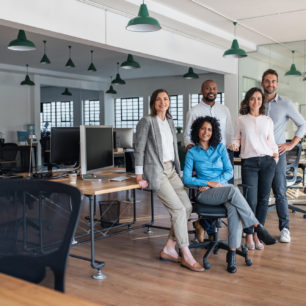 Portrait of a smiling group of diverse businesspeople working together in a modern open plan office